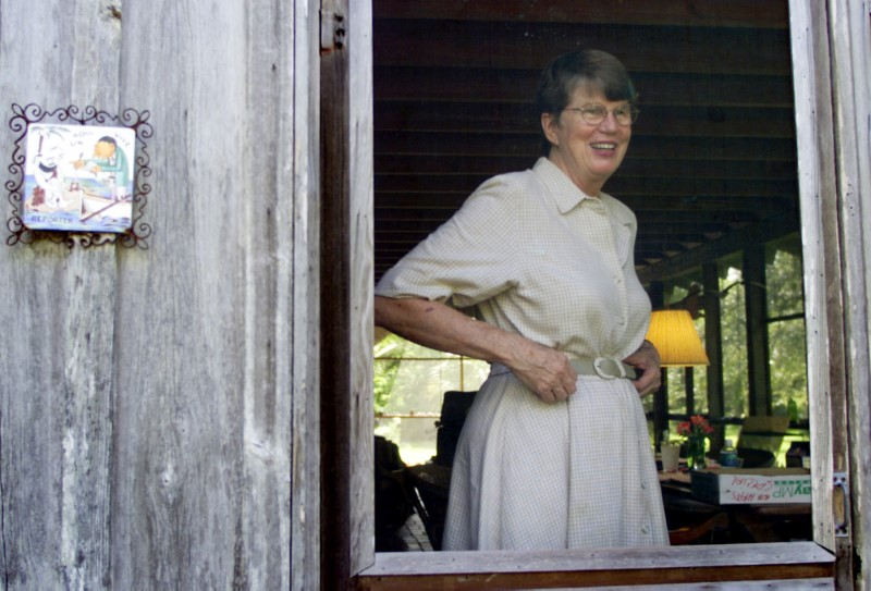 "Former U.S. Attorney General Janet Reno greets the media next to a caricature of a journalist and fisherman with the the saying in spanish ""A reporter lives here,"" at the back porch of her home in Miami, September 4, 2001. REUTERS/Colin Braley"