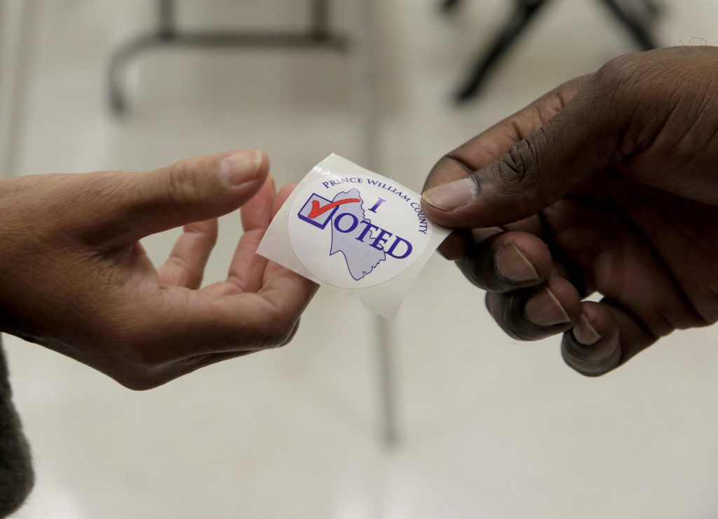 "A poll worker hands out an ""I voted"" sticker to a voter during the U.S. presidential election at Potomac Middle School in Dumfries, Virginia, U.S., November 8, 2016. REUTERS/Joshua Roberts"